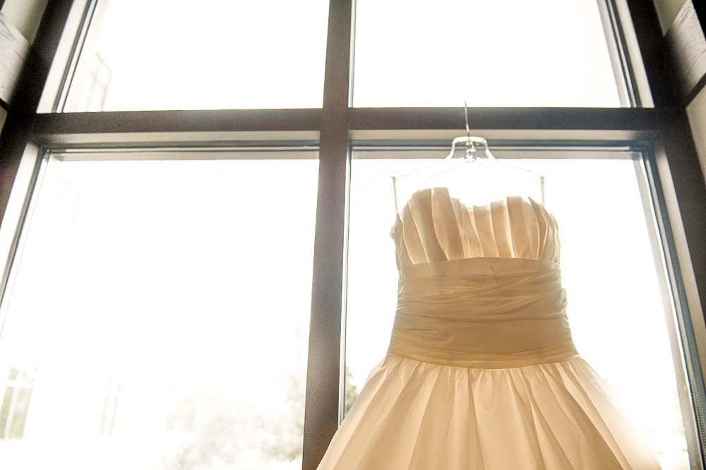 shot of wedding dress hanging in window