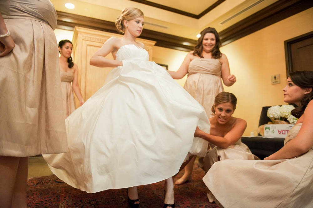 bride stepping into her shoes with assistance from her bridesmaids
