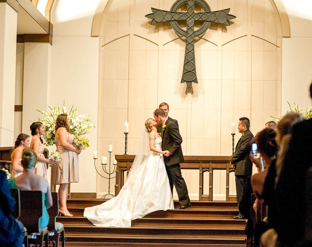 bride and groom kiss after reading vows to each other during wedding ceremony in houston texas
