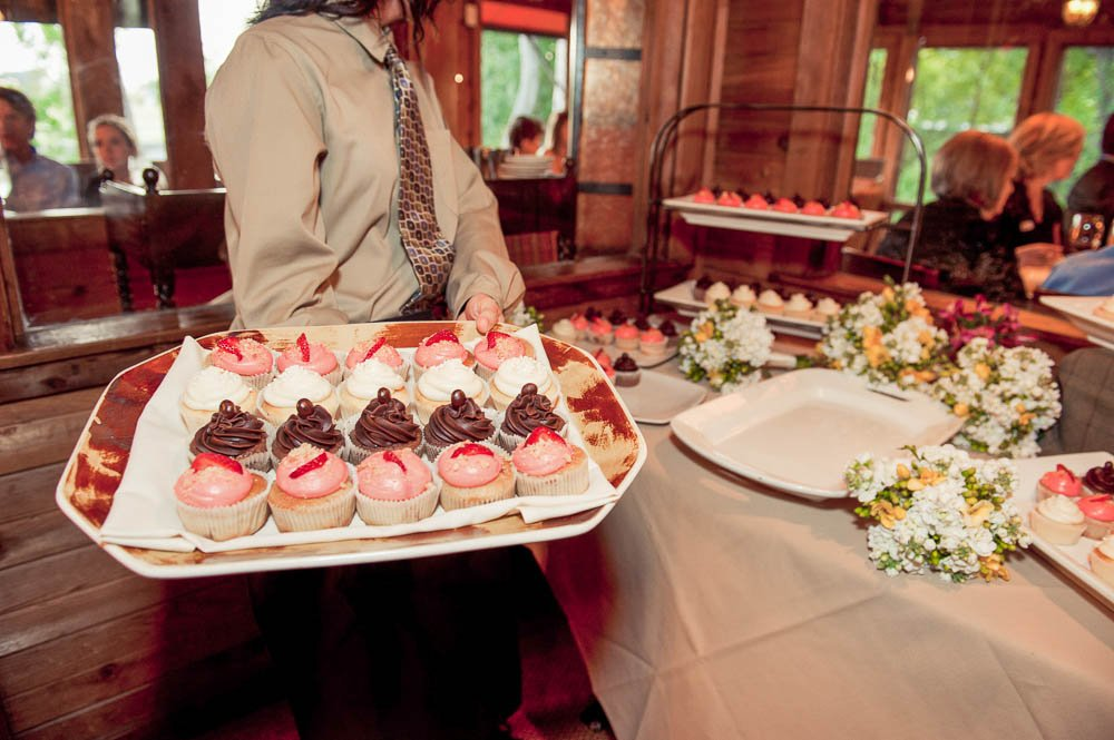 caterer sets out cupcakes at wedding reception in houston texas, rainbow lodge catering, cupcake desserts, cupcakes instead of cake
