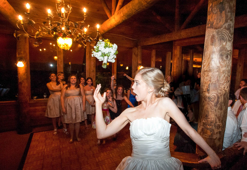 bride laughs as she tosses her whole bouquet to her friends below, rainbow lodge wedding houston texas, july 4th themed wedding in houston texas,