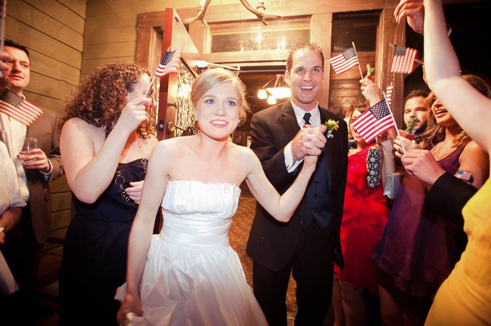 grand exit with american flags after rainbow lodge wedding reception in houston texas, rainbow lodge wedding reception photography, houston wedding photographer