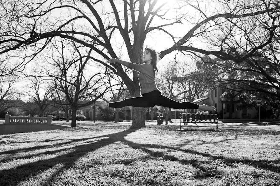 austin ballet dancer does leap in a park, austin portrait photography, black and white dancer photos
