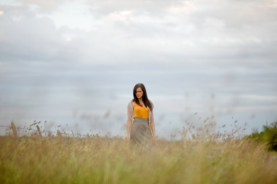 texas girl in field with cloudy skies, texas state graduation photography
