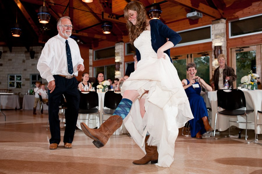 bride wearing cowboy boots and argyle socks dancing with her dad at Luther Hills Chapel in La Grange