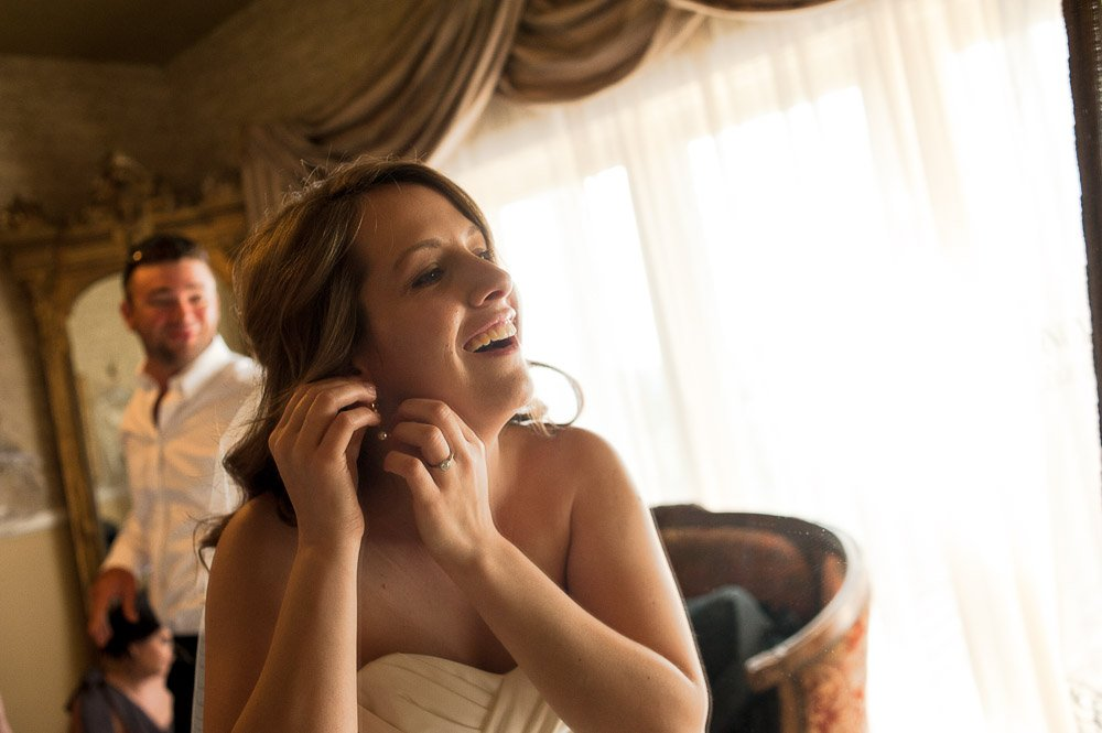 bride laughing as she puts her earrings on in the getting ready room at vintage villas hotels austin