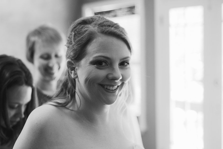 cedar bend events center, diy bride, black and white of bride smiling getting ready