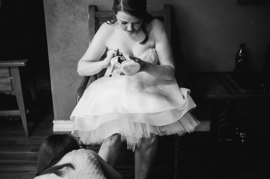 artistic black and white shot of bride putting shoes on Cedar Bend Events Center