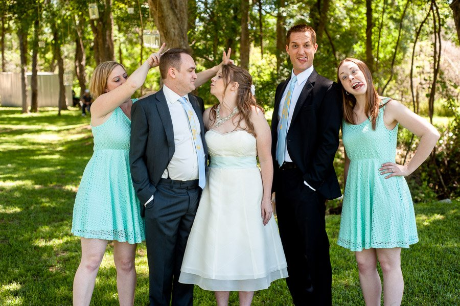 silly bridal party shot while bride and groom look at each other, cedar bend events center DIY wedding, vintage theme wedding