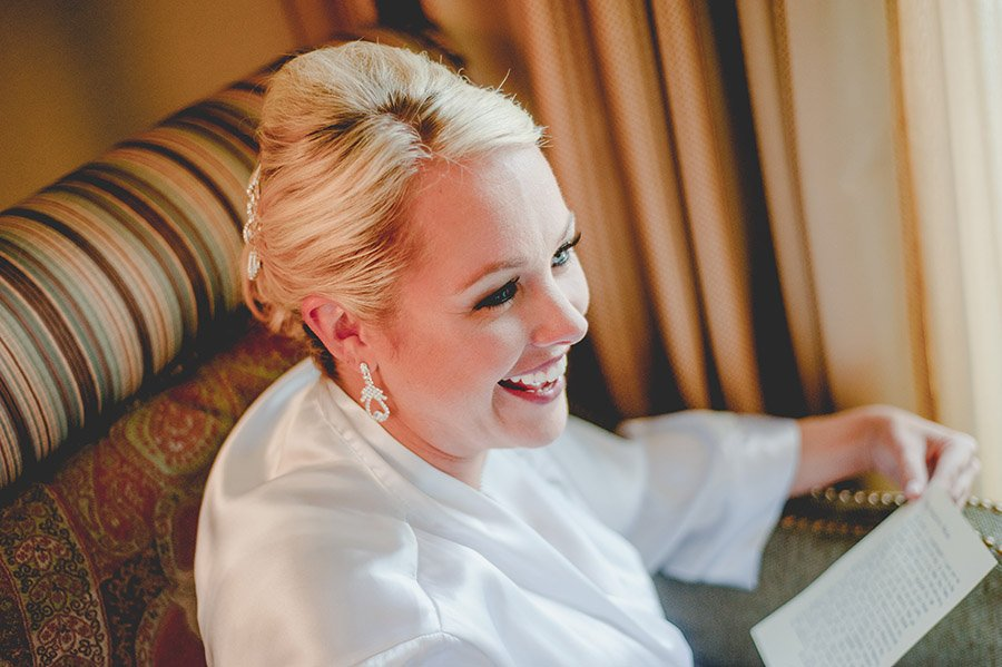 bride laughing in white robe getting ready, omni hotel downtown wedding,