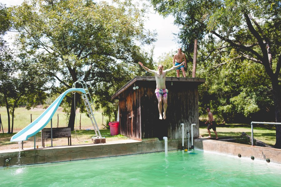 groom to be jumps into pool at family ranch in boerne before wedding day in San Antonio, Texas. Photo by Caitlin McWeeney Photography