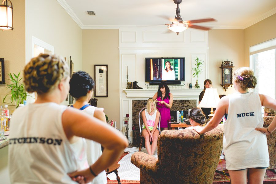 bridesmaids watch on as bride gets her hair done before her london comes to texas wedding in san antonio