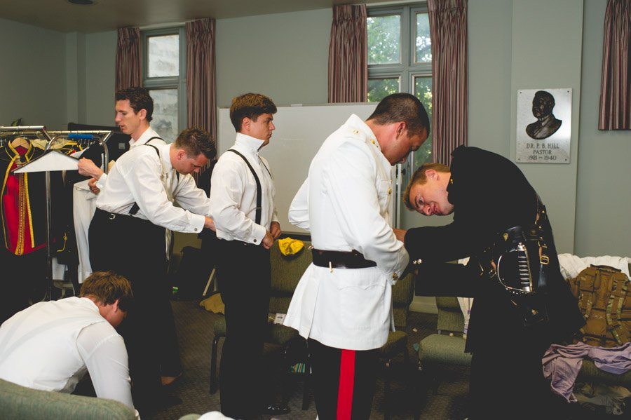 Groomsmen prepare uniforms and suits while getting ready at San Antonio church