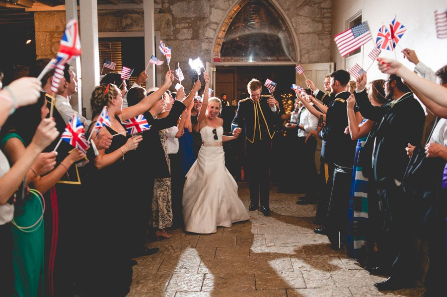 bride and groom grand exit with american and british flags at southwest school of art san antonio texas,