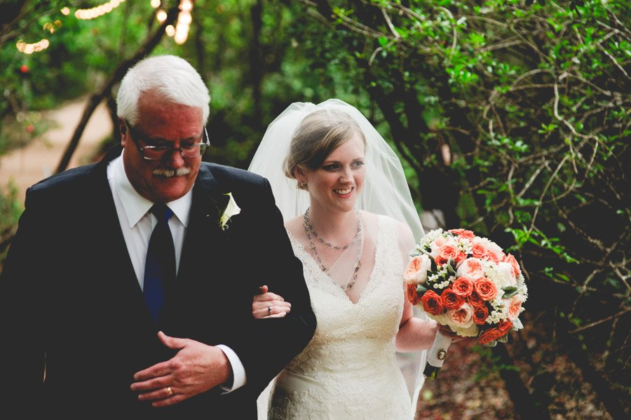 bride is escorted to the ceremony at laguna gloria by her father, pink and yellow flower bouquet, blusher veil, classic black tie suit for father of the bride, austin wedding photography, central texas wedding photographer, travel wedding photography in austin