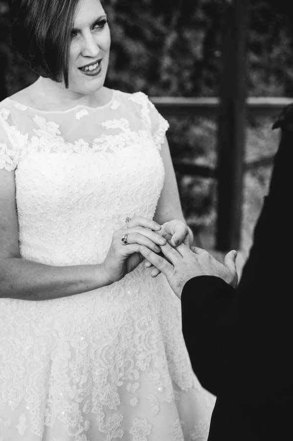 bride and groom exchange rings after saying their vows