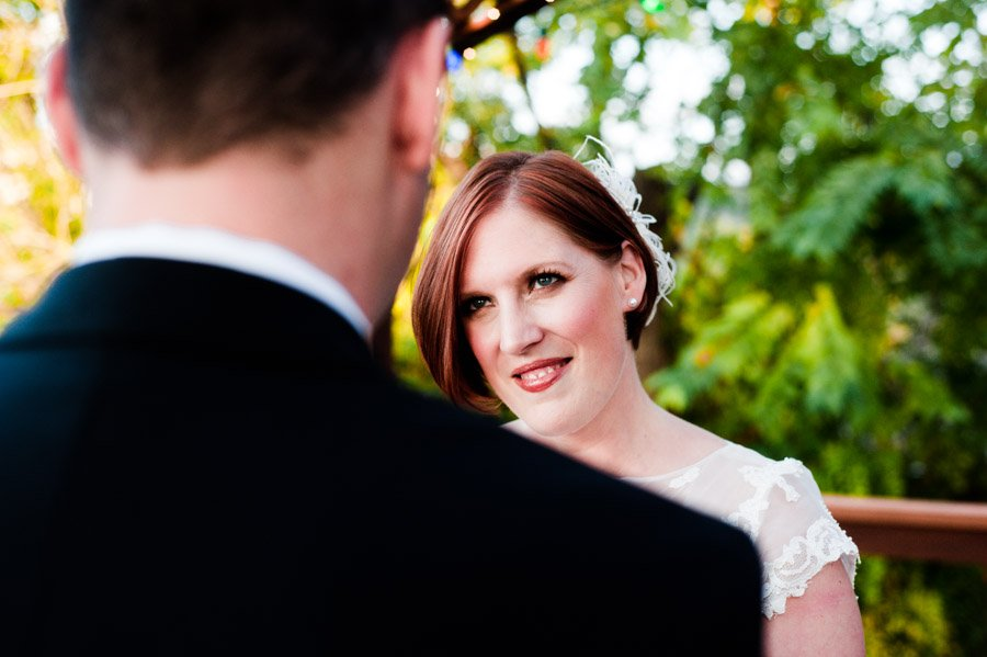 austin fall backyard elopement photography, bride smiling at her groom during vows at a lakeside elopement in austin, private residence mini wedding in Austin