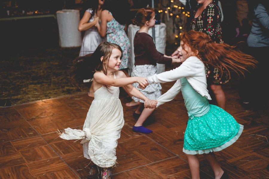 little girls dancing together at an austin farm wedding