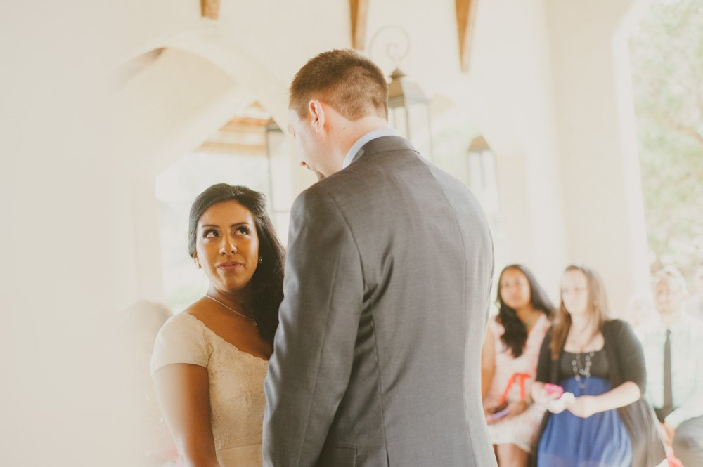 bride teary eyed looking at her husband during vows