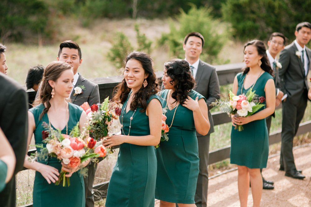 happy wedding party in teal before the ceremony, matching teal bridesmaids dresses and guys in grey suits, wild floral arrangement for bouquets, peony and ranunculus bouquets