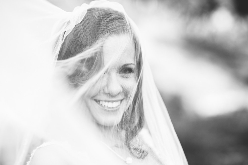 black and white bride smiling under veil during bridals