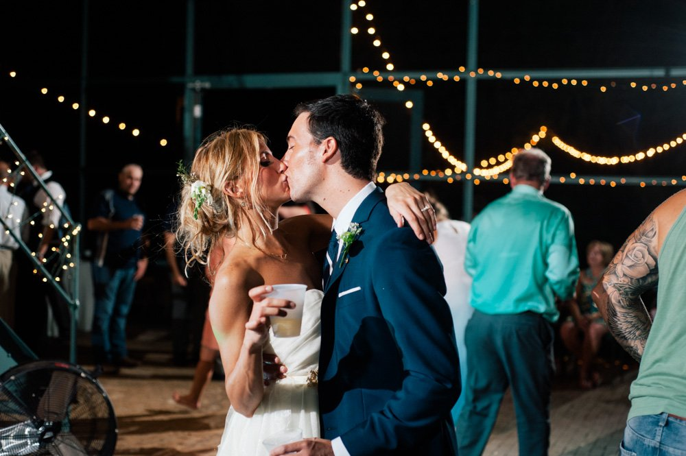 austin wedding photographer the plant at kyle, french bohemian wedding photographer, bride and groom kiss at the end of the night, the plant at kyle reception summer wedding