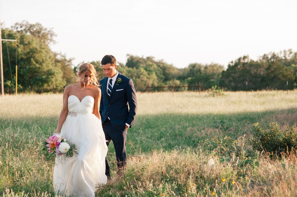 romantic sunset photos at the plant at kyle, bride and groom portraits in a field at sunset, bohemian chic wedding photography style, timeless wedding photography in austin