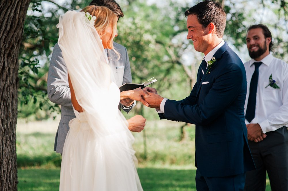 wedding ceremony under the trees, natural light wedding photographer in kyle, exchange of rings wedding photographer plant at kyle