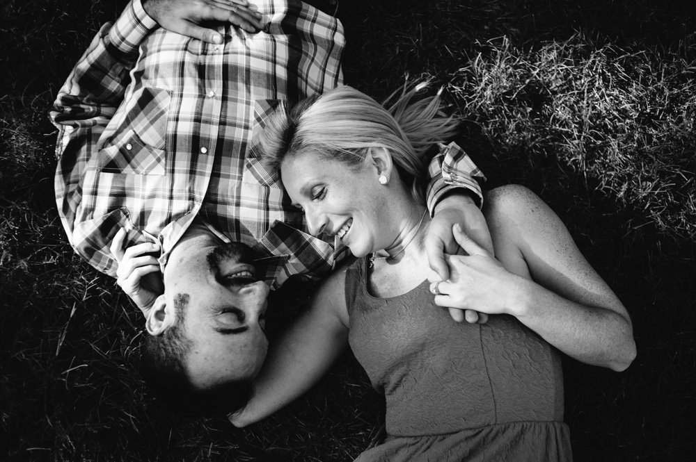 black and white of couple holding hands on the grass