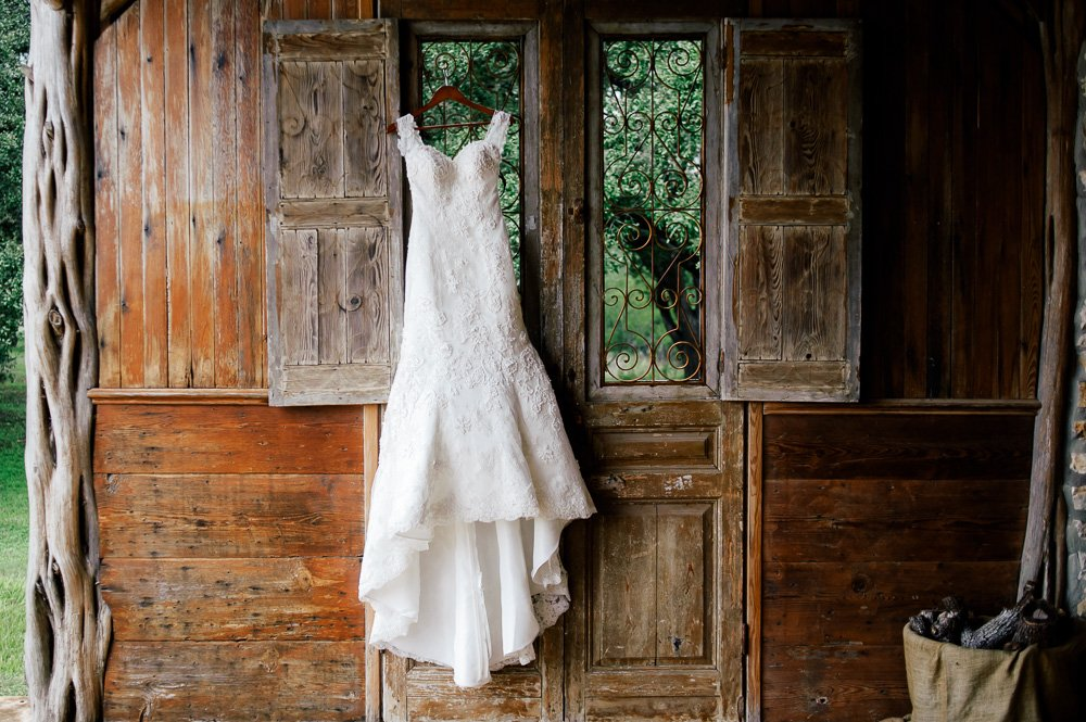 dress hanging on rustic iron wall in wimberley texas, old glory ranch dress shot, fall at old glory ranch, justin alexander rustic wedding dress