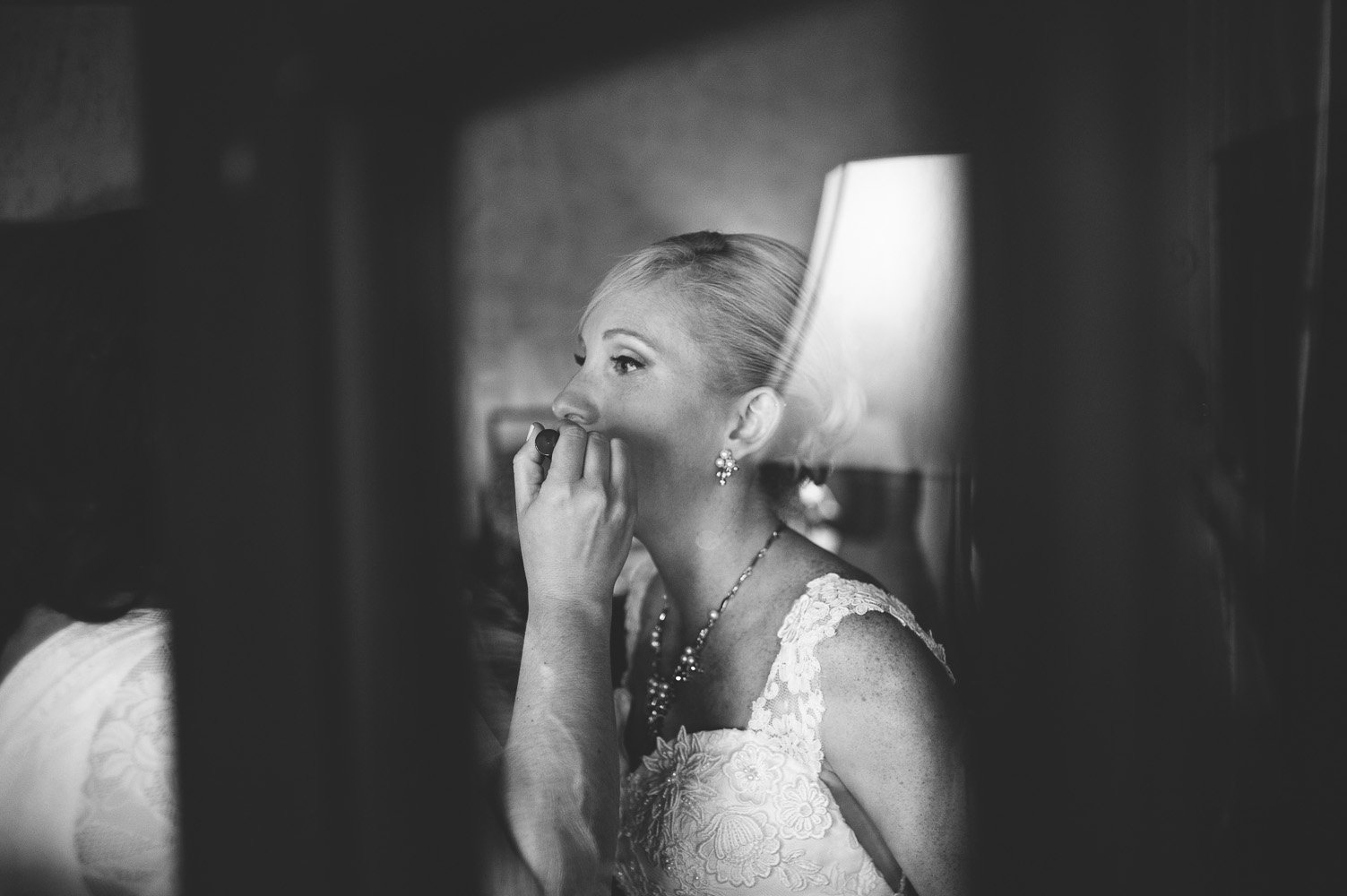 bride getting ready, black and white of bride in a lace dress applying lip gloss, pre wedding photography, black and white wedding photography at old glory ranch,