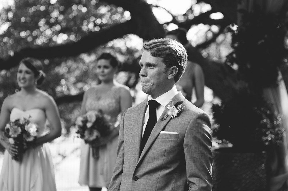 groom in tears as the bride approaches, black and white groom photo, wild onion ranch wedding photographer, wild onion ranch wedding photography, grooms reaction shot at austin hill country venue.