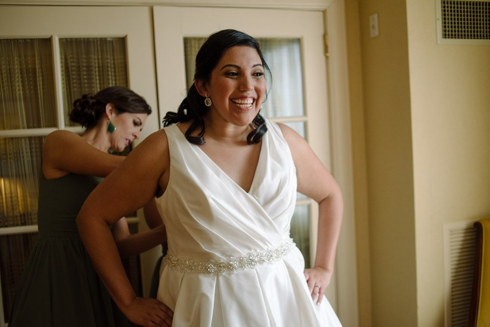 modern mercury hall wedding, bride laughing getting into her dress, getting dressed for a wedding,
