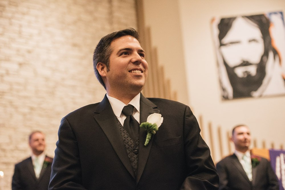 groom smiles at bride