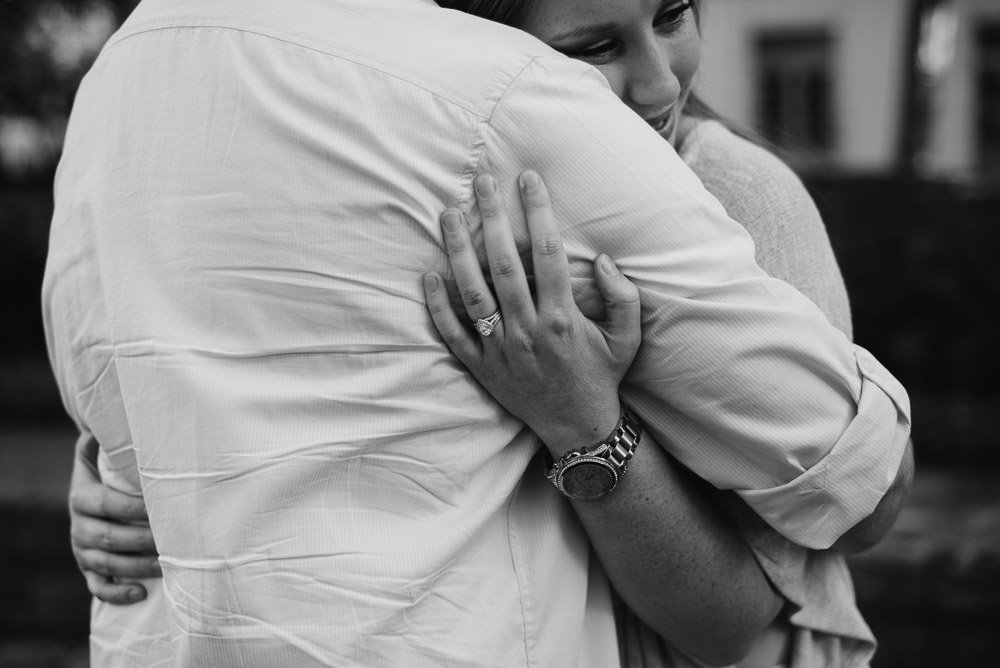 a newly engaged girl hugs her fiancee and shows off her ring