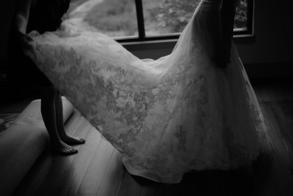moody black and white of bride getting into her dress
