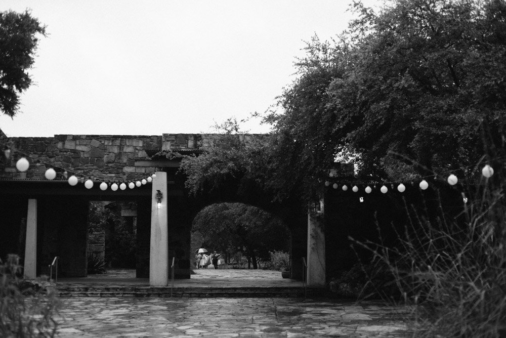 the bride and her attendants arrive for her rainy may wedding at the wildflower center in austin