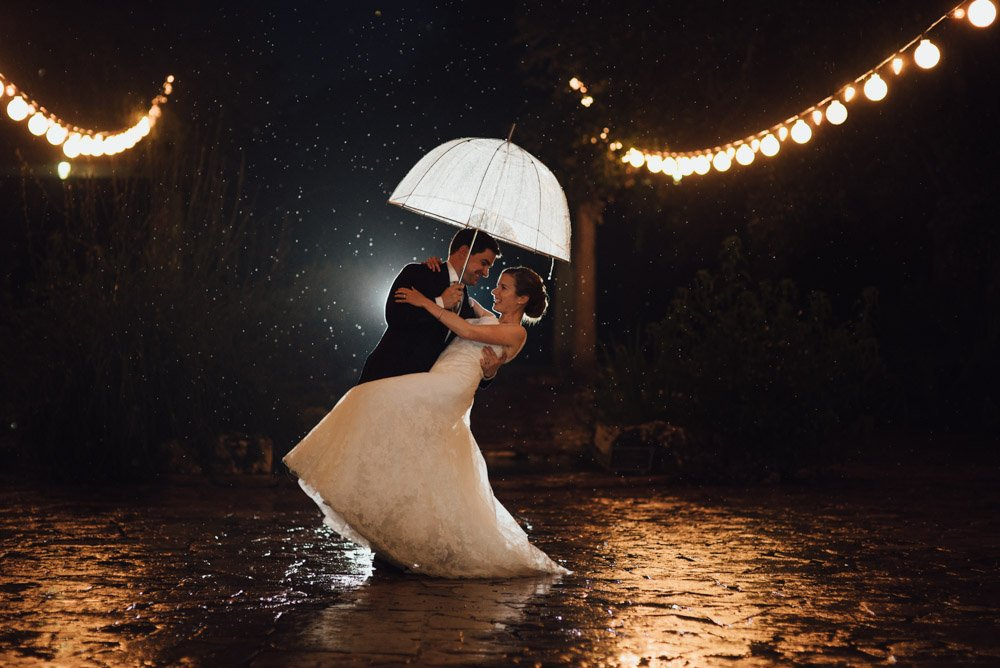 groom dips his bride for a dramatic rainy wedding photograph in austin texas