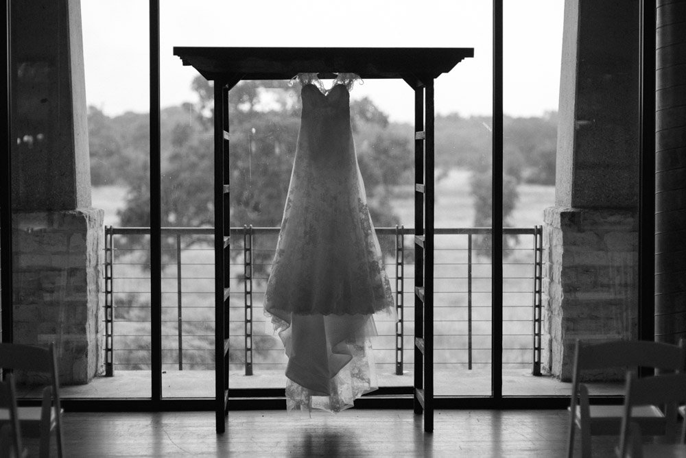 black and white photo of a watters on a rustic wooden arbor at the ladybird johnson wildflower center for a may wedding