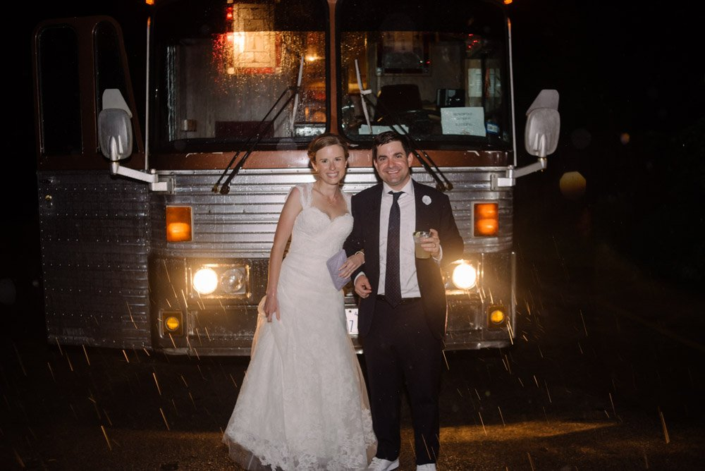 bride and groom in front of willie nelson's old tour bus