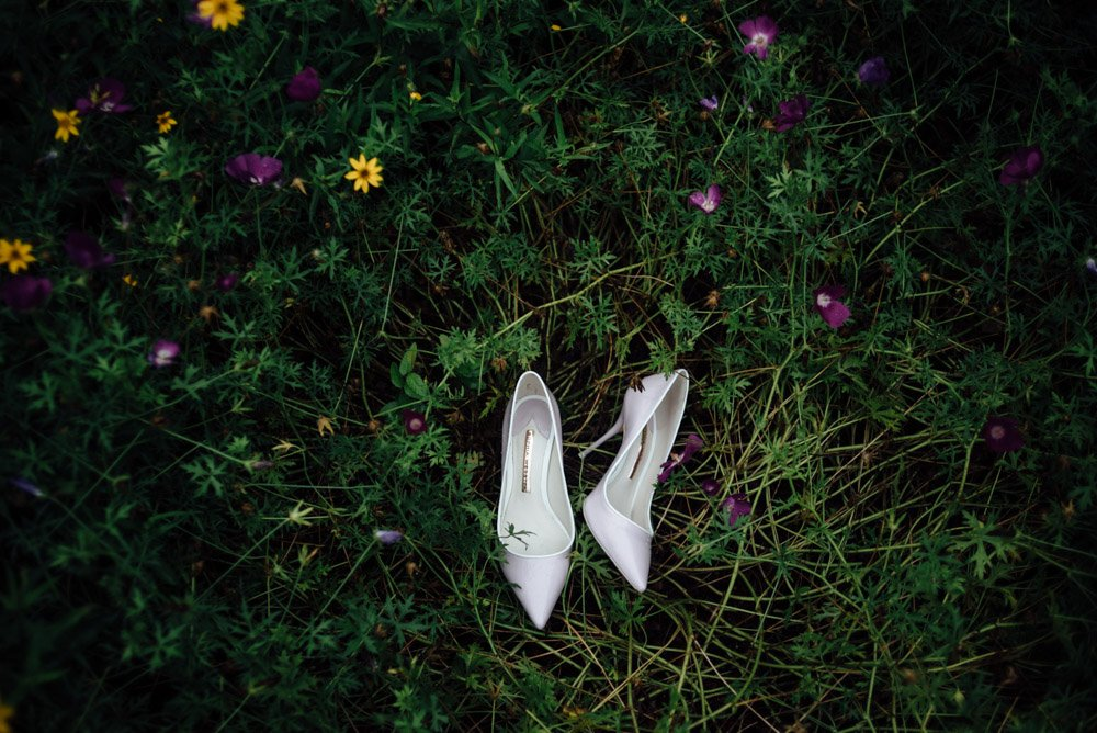 the bride's personal lavender pumps lay in the grass among texas wildflowers at a may wedding in austin texas