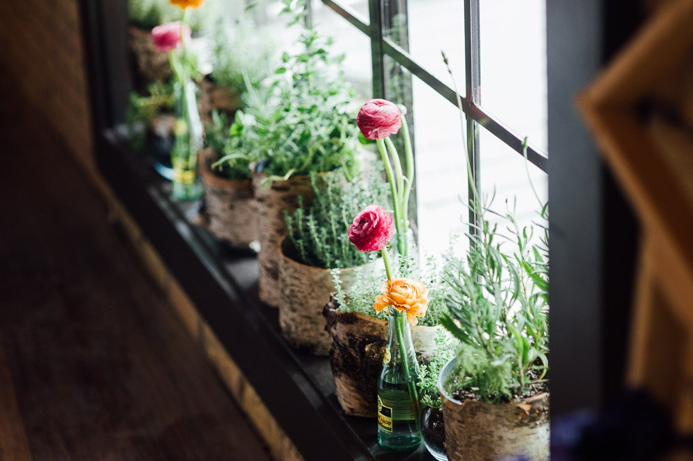 succulents and pink flowers in topo chico bottles at the waller ballroom