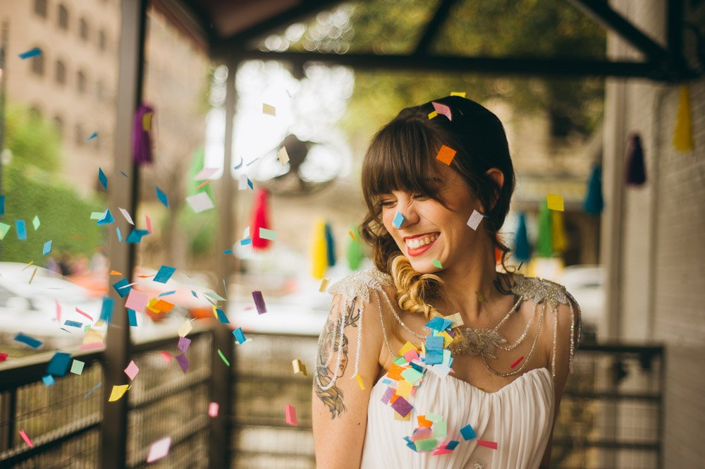 bride laughing as multi colored confetti flies all around her at the waller ballroom in austin