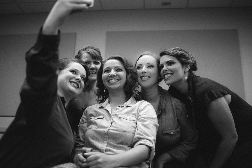 bridesmaids taking selfies while getting ready at at&t center, bob bullock museum wedding prep