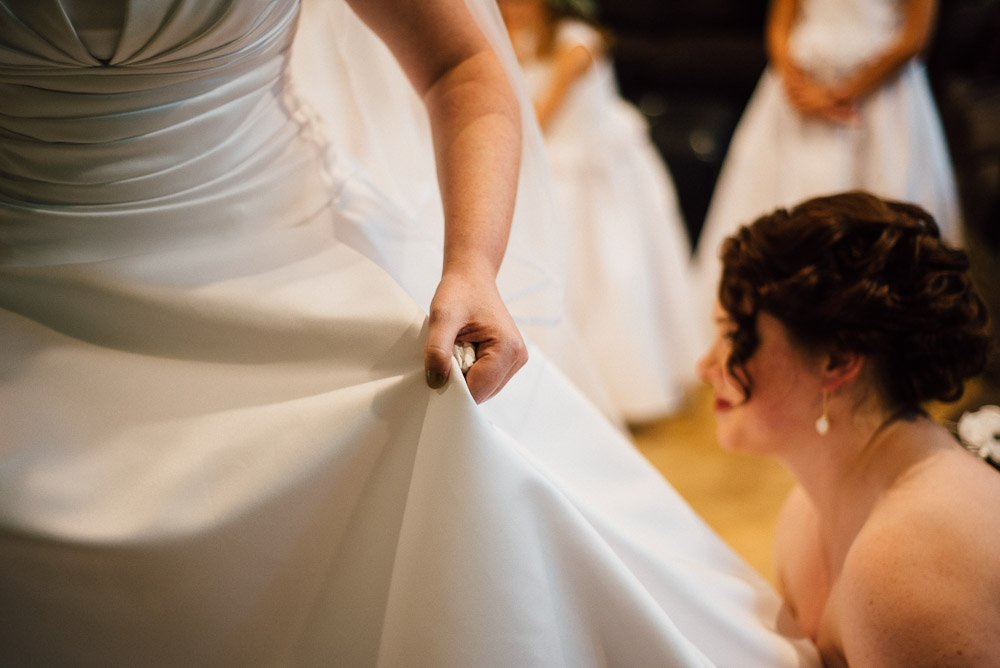 bride getting dressed in pronovias at university baptist church