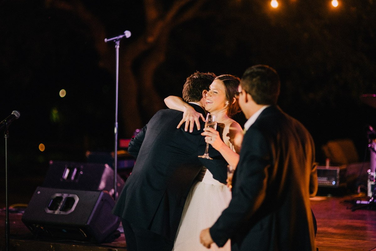 bride hugs the best man after a humorous toast about their med school days together at university of texas austin, wedding photographer to UT alumni in austin texas