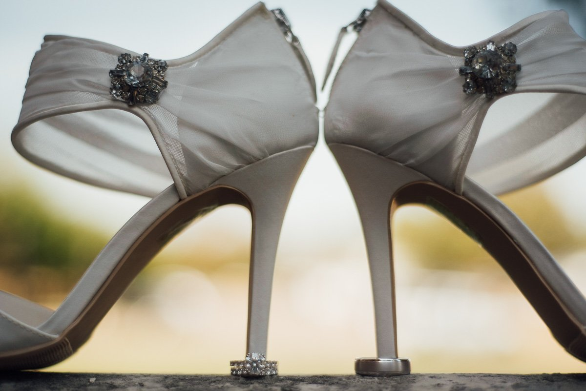 creative daytime ring shot with bride's shoes
