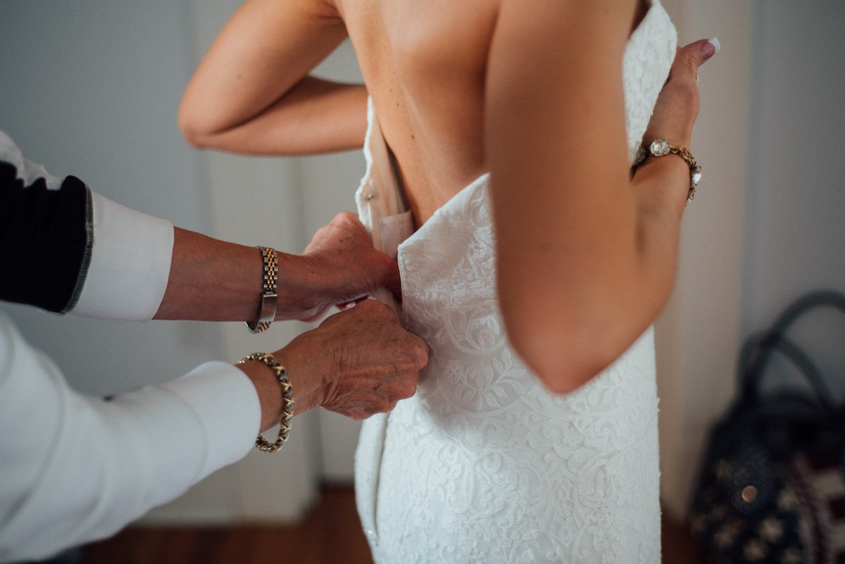 romantic detail of bride getting her dress zipped by her mom