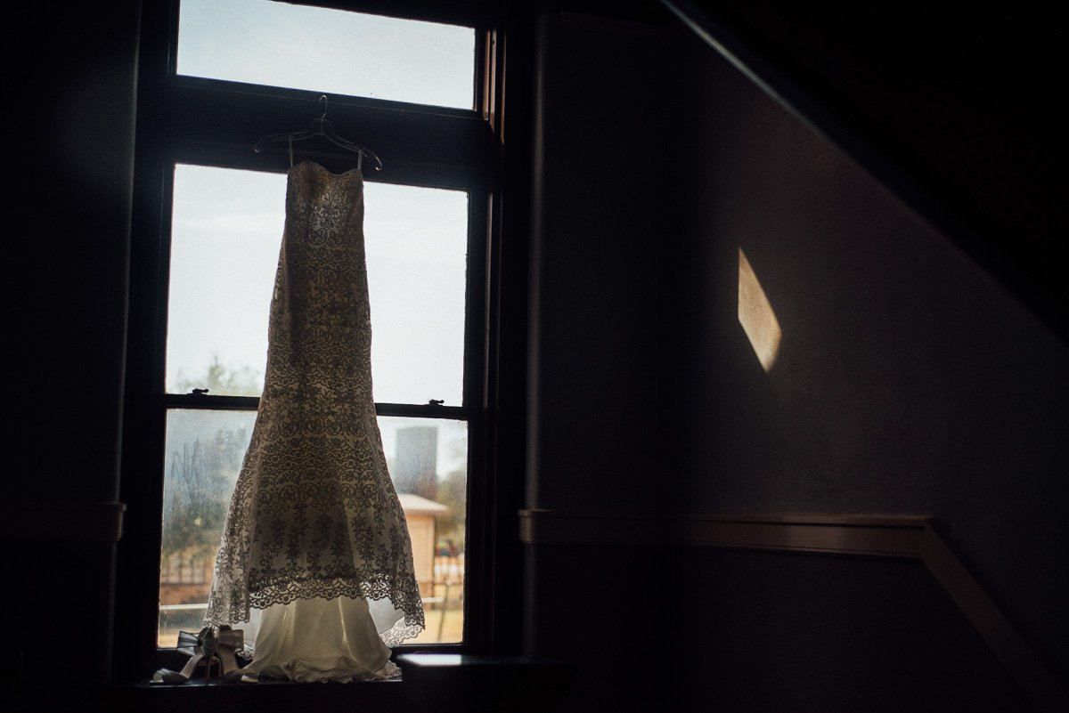 wedding dress hanging from window at a winter victory arts center wedding in fort worth, creative fort worth wedding photography, elegant winter wedding for dallas and fort worth couples
