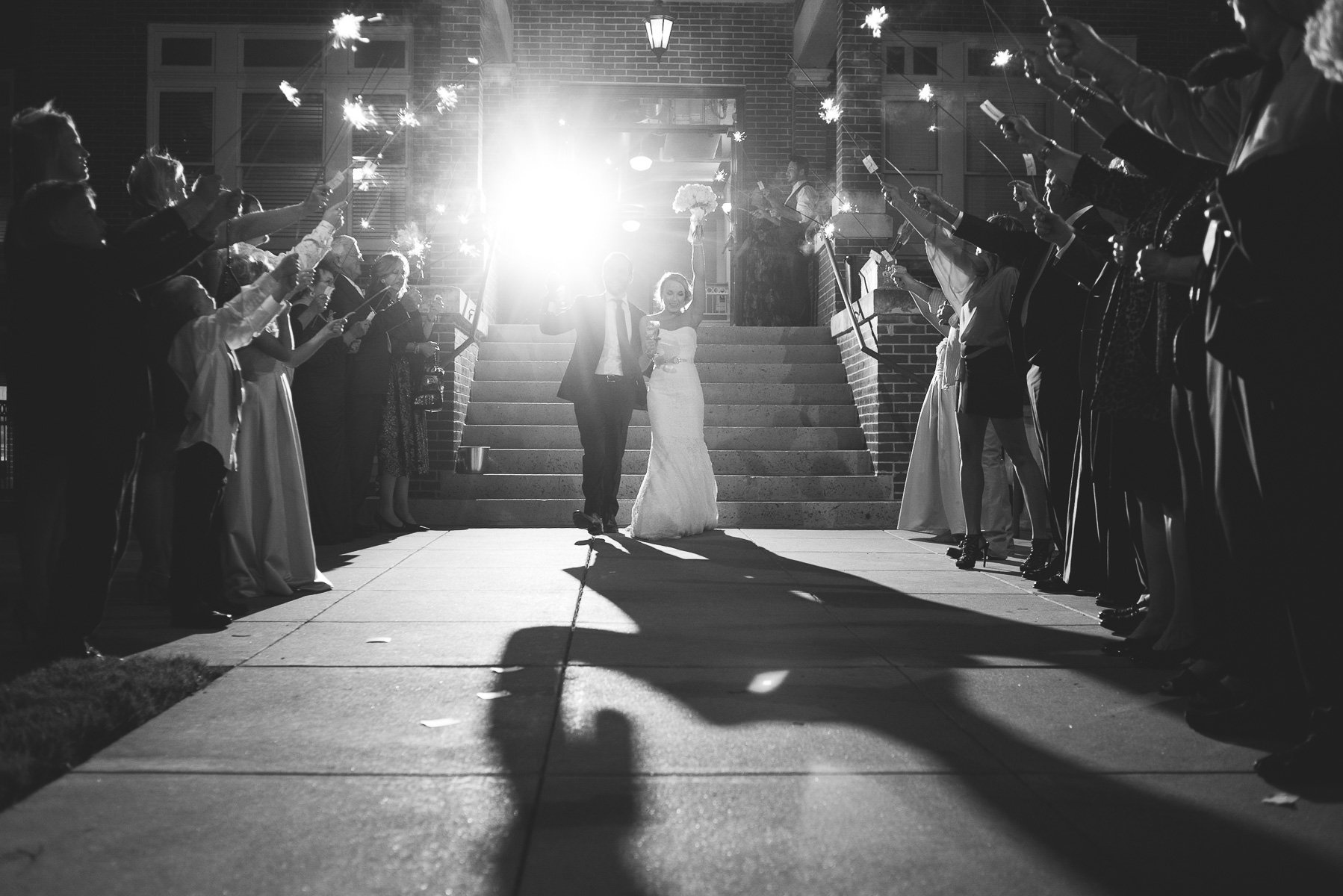 the couple has a grand exit with sparklers after a classic gold glam wedding in texas